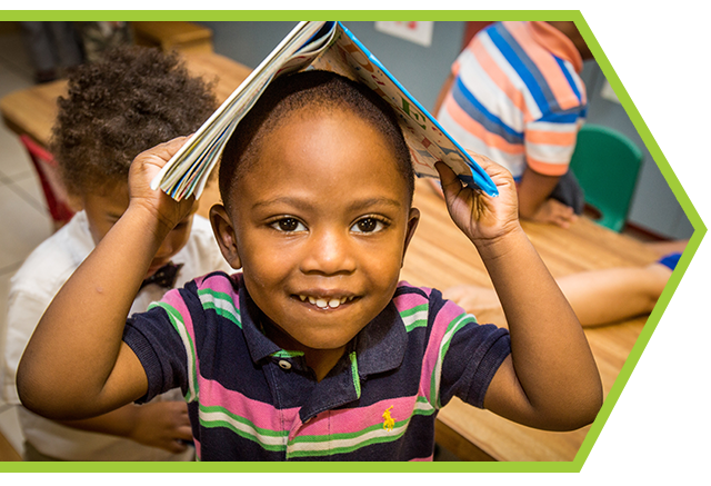 African-american boy enjoys reading time at a Preschool & Daycare Serving Palm Springs, Lake Worth, West Palm Beach, FL