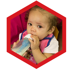 Cute baby drinking a bottle of milk at a Preschool & Daycare Serving Palm Springs, Lake Worth, West Palm Beach, FL